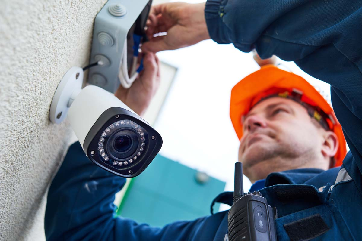 Video surveillance. Technician worker installing wall camera with screwdriver
