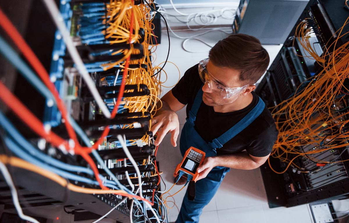 Top view of young man in uniform with measuring device that works with internet equipment and wires in server room.